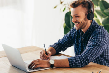 smiling man in headphones taking part in webinar at tabletop with notebook in office